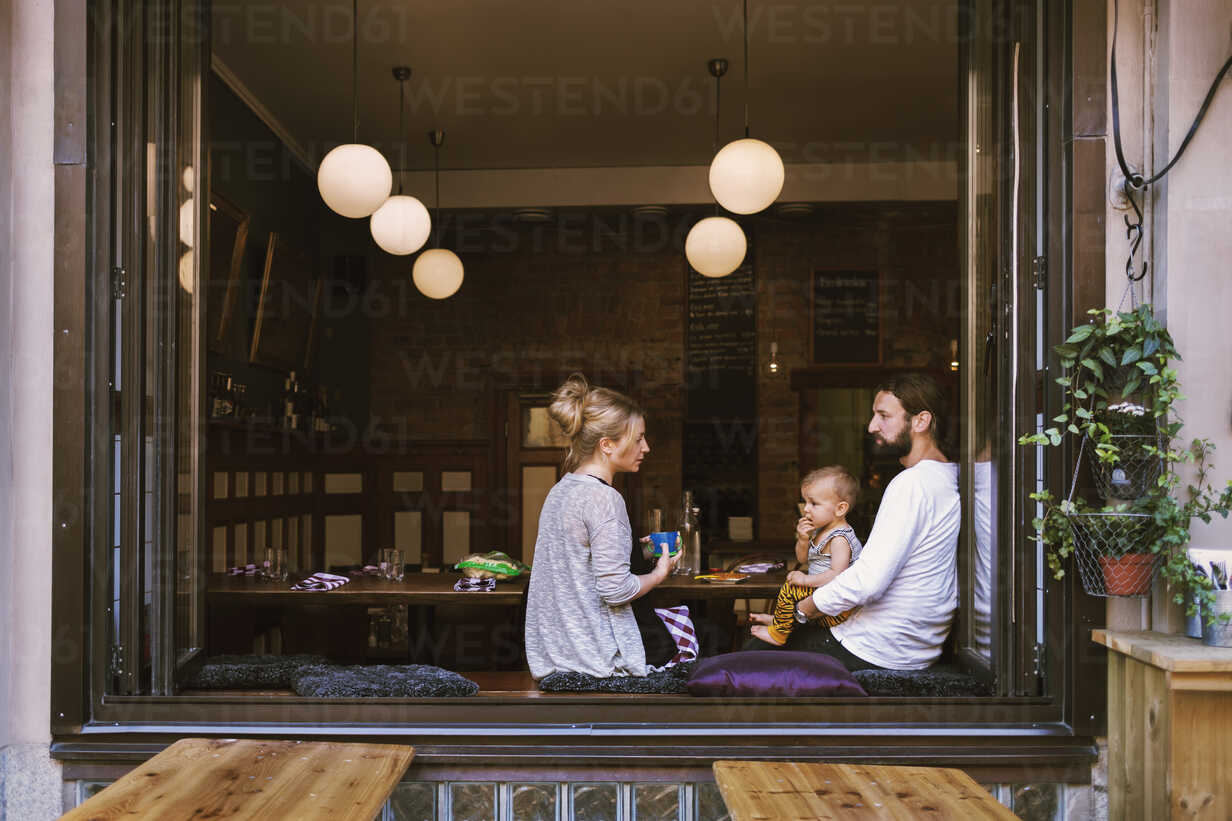 Mid adult parents with son in restaurant seen through window - MASF04188 - Maskot ./Westend61