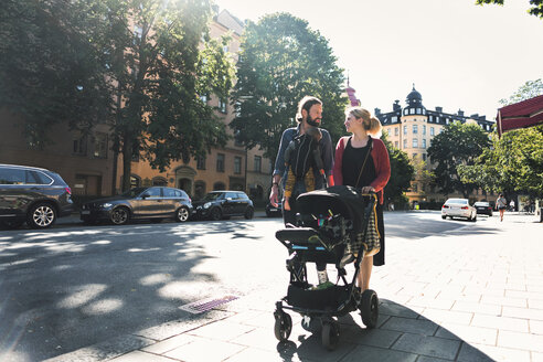 Mid adult parents with baby boy and stroller walking on sidewalk in city - MASF04194