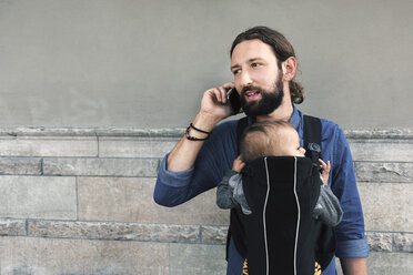 Mid adult man using mobile phone while carrying son in baby carrier against wall - MASF04197