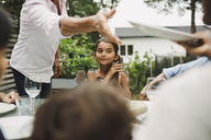 Midsection of senior woman taking plate from daughter-in-law at outdoor dining table - MASF04203