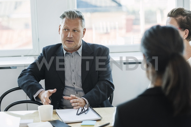 Mature businessman sitting and explaining coworkers at office - MASF04209