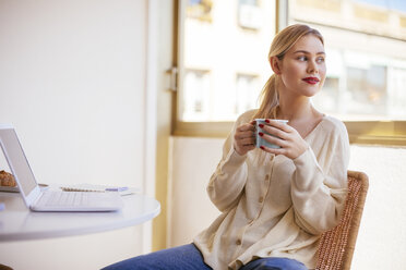 Blonde woman with cup of coffee looking out of the window - EBSF02390