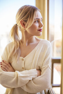 Blonde woman looking out of window - EBSF02393