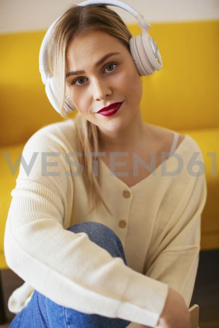 Blonde woman with headphones using smartphone at home - EBSF02408 - Bonninstudio/Westend61
