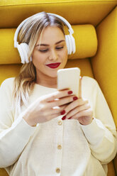 Blonde woman with headphones using smartphone at home - EBSF02411