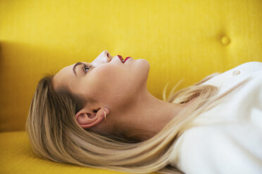 Blonde woman lying on sofa - EBSF02414