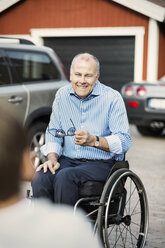 Happy father in wheelchair looking at son on street - MASF04217