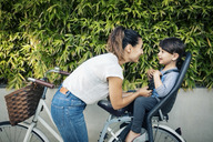 Happy woman looking at son sitting on back seat of bicycle against plants - MASF04226