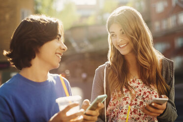 Happy teenagers looking at each other while holding smart phones outdoors - MASF04241