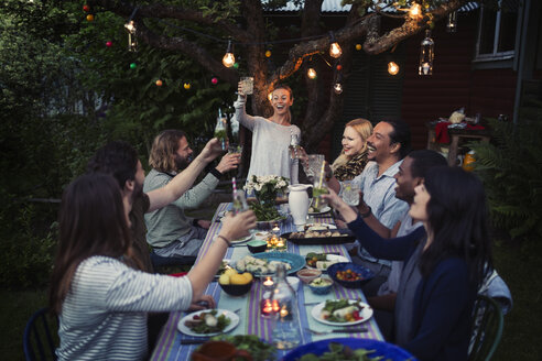 Happy woman toasting drink to friends at dining table while enjoying outdoor dinner party - MASF04247