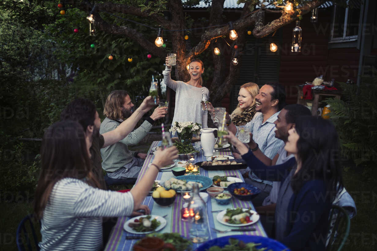 Happy woman toasting drink to friends at dining table while enjoying outdoor dinner party - MASF04247 - Maskot ./Westend61