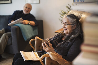 Happy senior woman using mobile phone while man sitting on sofa at home - MASF04274