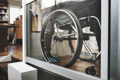 Low section of son and father in wheelchair lift at home - MASF04280