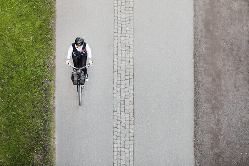 High angle view of businesswoman riding bicycle on road - MASF04283