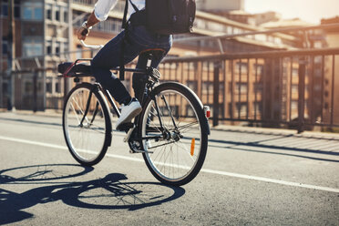 Low section of businessman riding bicycle on bridge in city - MASF04286