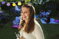 Happy young woman with friends in background at yard during summer party - MASF04316