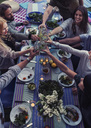 High angle view of multi-ethnic friends toasting drinks at dinner table in yard - MASF04319