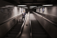 Low angle view of businessman with luggage checking time on escalator in airport - MASF04331