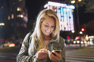 Happy young woman using smart phone on city street at night - MASF04334