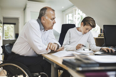 Disabled father assisting son in doing homework at home - MASF04349