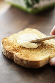 Cropped hand applying butter on bread toast - MASF04361