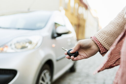 Cropped image of businesswoman using remote control key to unlock car - MASF04364