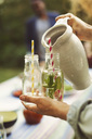 Cropped image of woman serving mojito in bottle at summer party - MASF04376