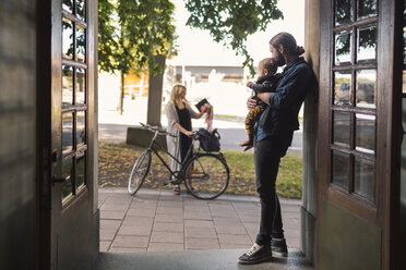 Father at door holding baby while looking at woman leaving for work - MASF04379