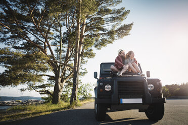 Couple sitting on jeep at countryside - MASF04382