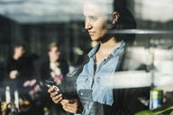 Close-up of young woman using smart phone seen through glass - MASF04385