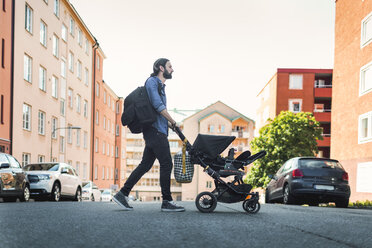 Full length side view of man pushing baby in carriage crossing city street - MASF04418