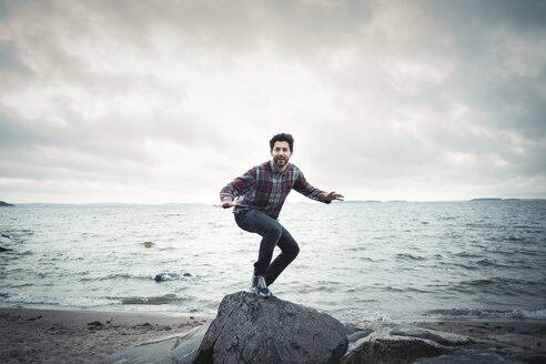 Full length portrait of happy man on rock by sea against cloudy sky - MASF04424