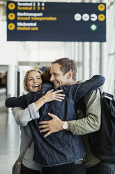 Happy business colleagues embracing at airport - MASF04427