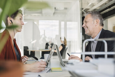 Happy businessman having discussion with colleague at desk - MASF04430