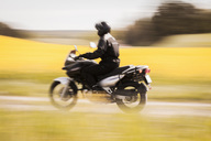 Blurred motion of man riding motorcycle on road amidst field - MASF04436