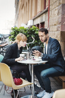 Business commuters using smart phone at sidewalk cafe - MASF04439