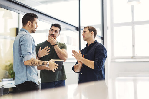 Businessman having discussion with male colleagues in office - MASF04463