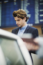 Businessman standing at airport check-in counter - MASF04481