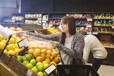 Young woman shopping fruits at supermarket with man in background - MASF04496