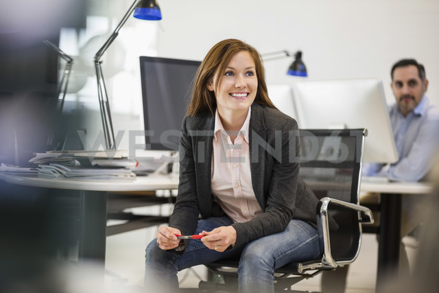 Smiling businesswoman looking away with colleague in background at office - MASF04505