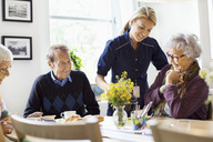 Smiling female caretaker serving coffee to senior people at nursing home - MASF04517