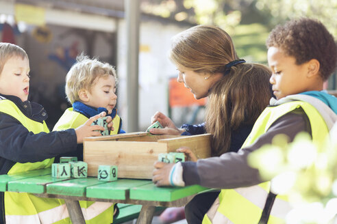 Teacher and children playing with blocks outside - MASF04529