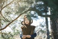Thoughtful girl in monkey suit standing by tree at yard - MASF04541