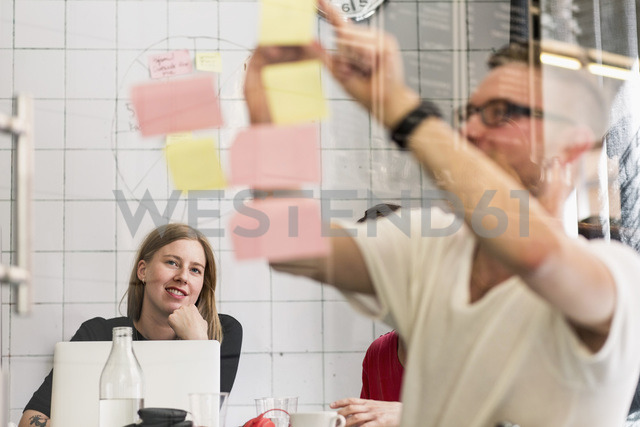 Young businessman writing ideas on adhesive notes with colleagues in background at creative office - MASF04556
