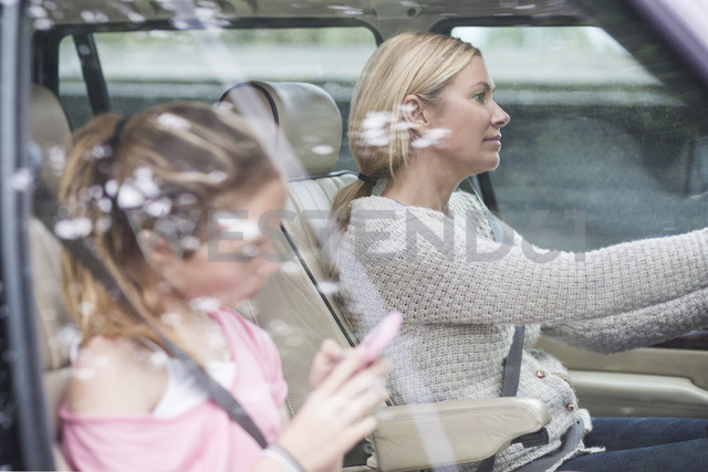 Woman driving while daughter using mobile phone in car - MASF04565