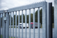 Trucks on road in front of metal gate - MASF04568