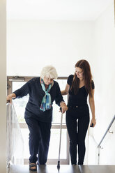 Young woman helping grandmother to climb steps - MASF04586