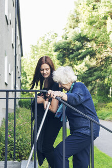 Young woman helping grandmother to climb steps outdoors - MASF04589