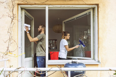 Woman and man cleaning window together - MASF04592