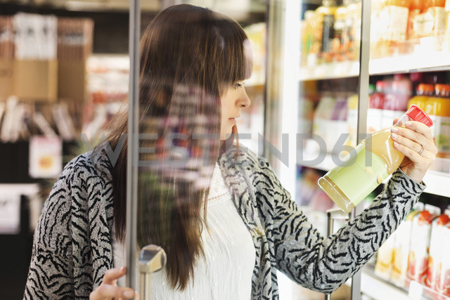 Young woman reading label on juice bottle at refrigerated section in supermarket - MASF04598